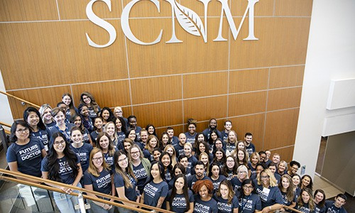SCNM | Group of people under SCNM sign
